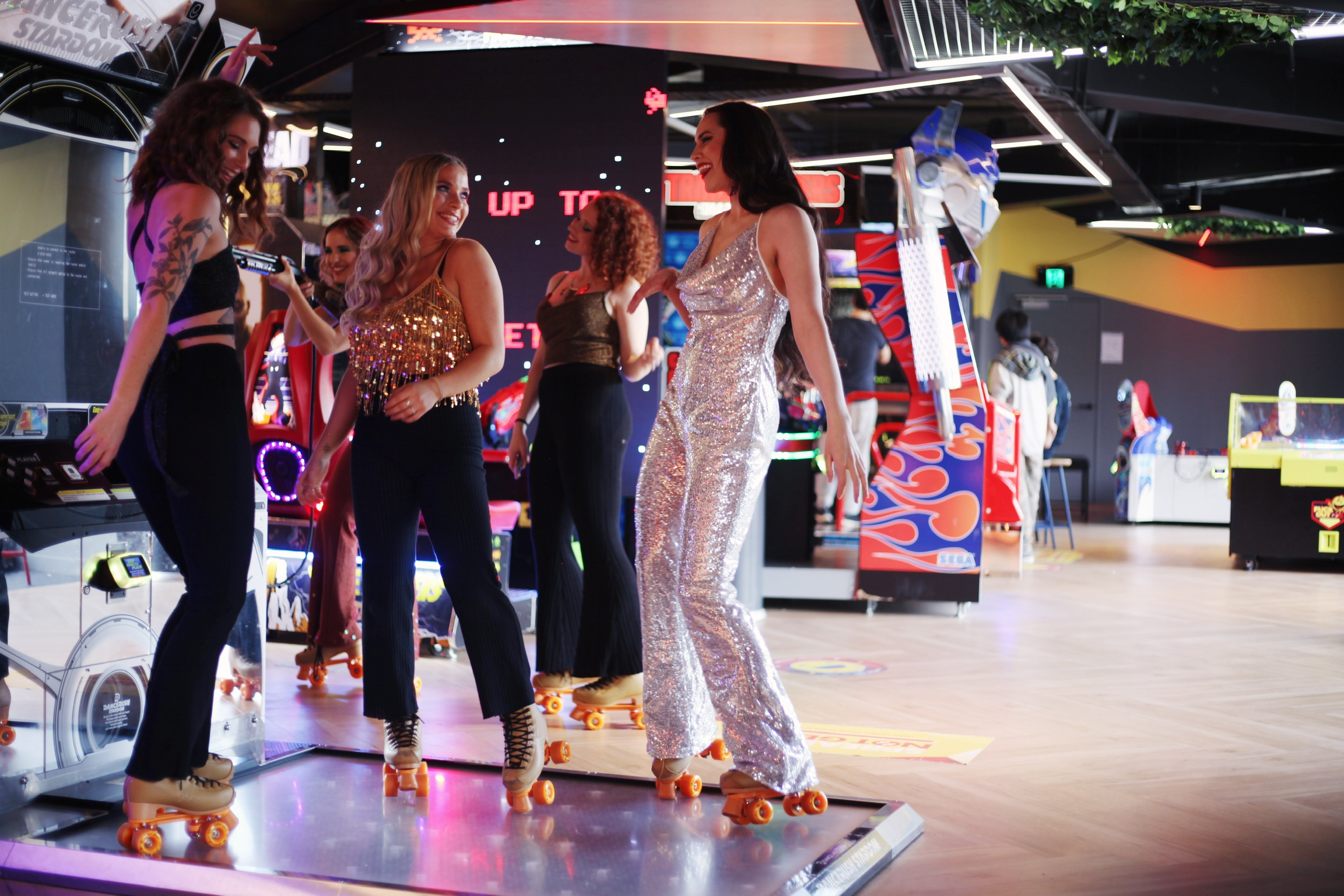 roller skating girls dance inside an arcade looking happy and smiling