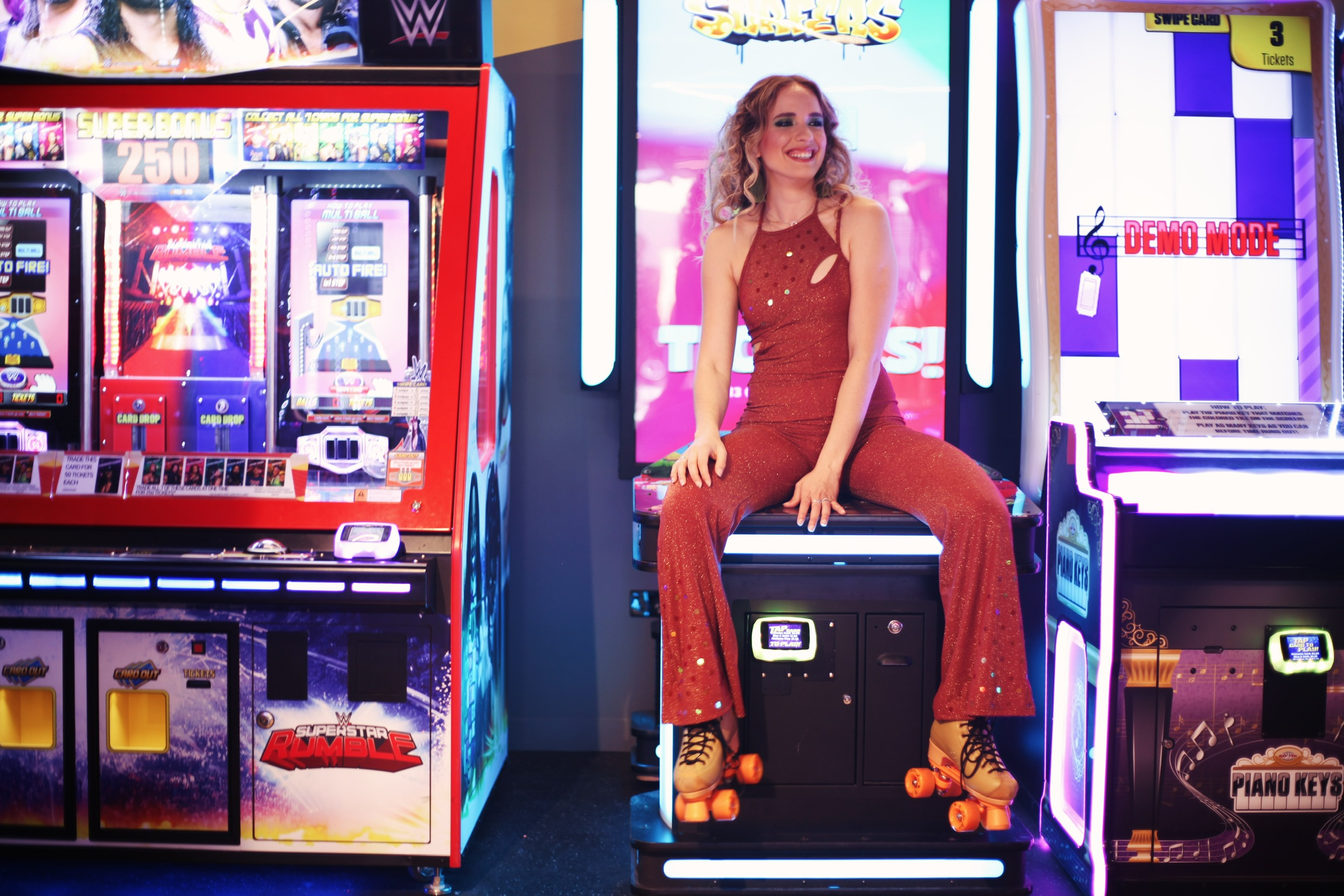 girl in roller skates sitting on arcade game smiling into the distance