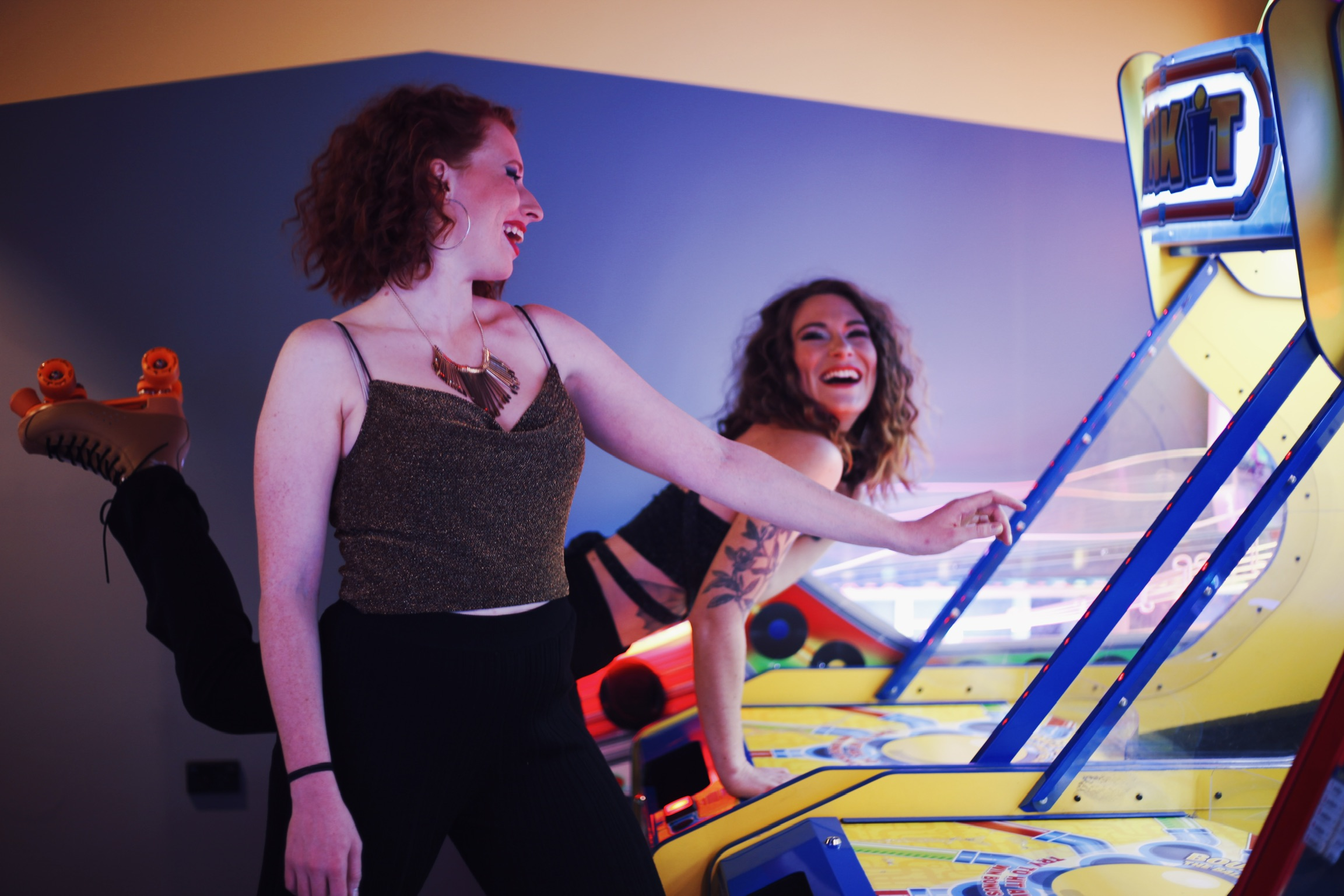girls laghing and playing arcade games