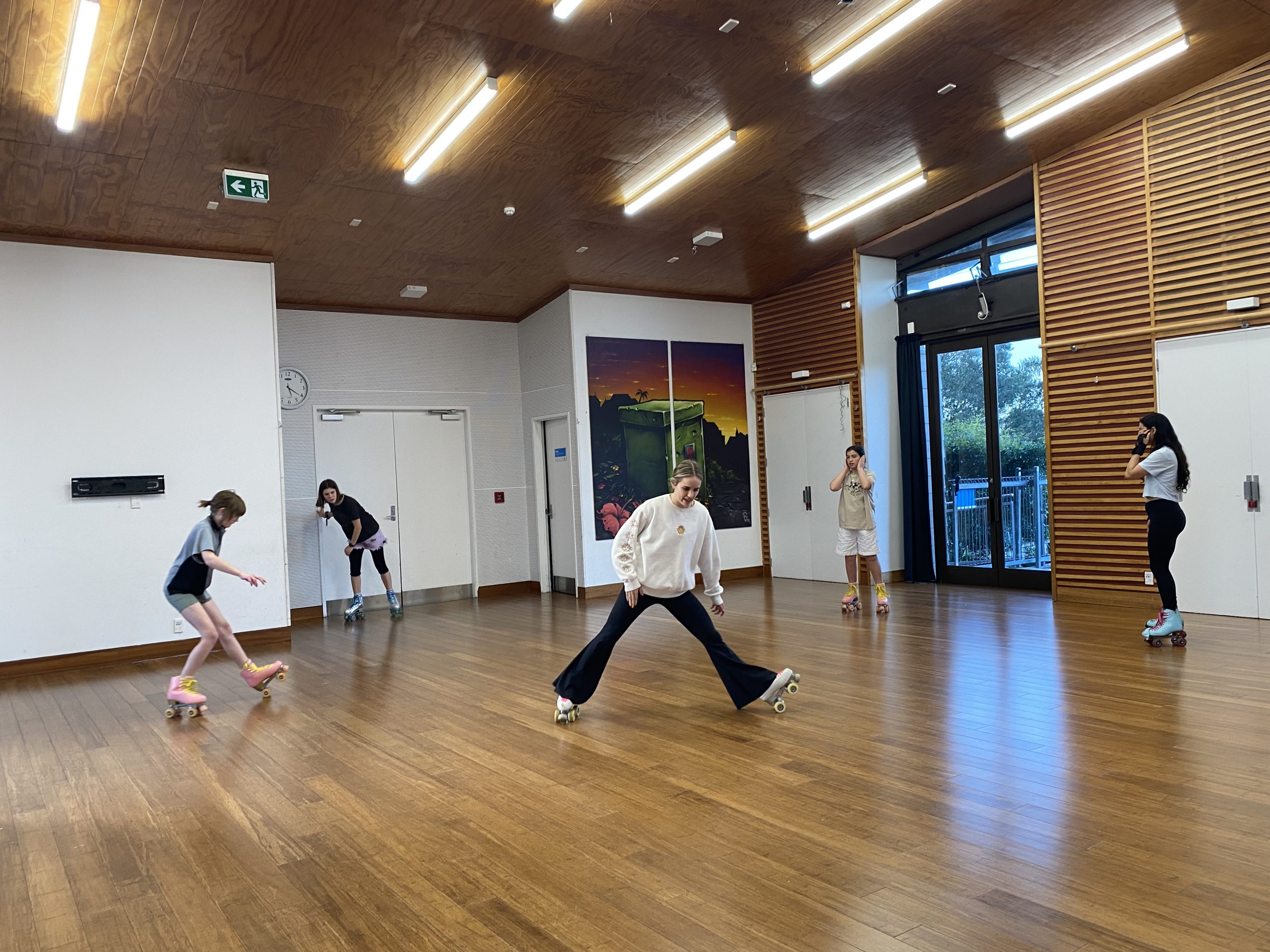 macarena teaches roller skating to a group of skaters in Grey Lynn Community Centre